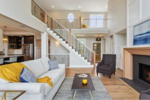open concept living room with stairs leading to second floor. designed with a white couch and grey rug to section off living space
