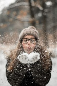 girl in snow attire blowing snow out of her out stretched hands